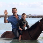 Father and son on horse at Pearly Beach